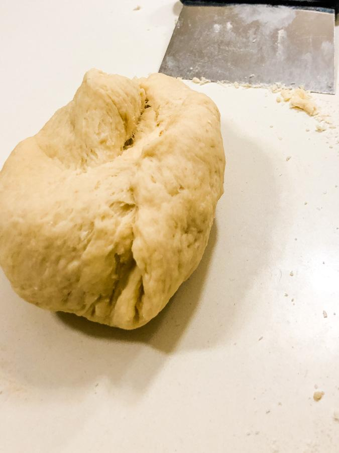 ball of croissant dough on bench with scraper