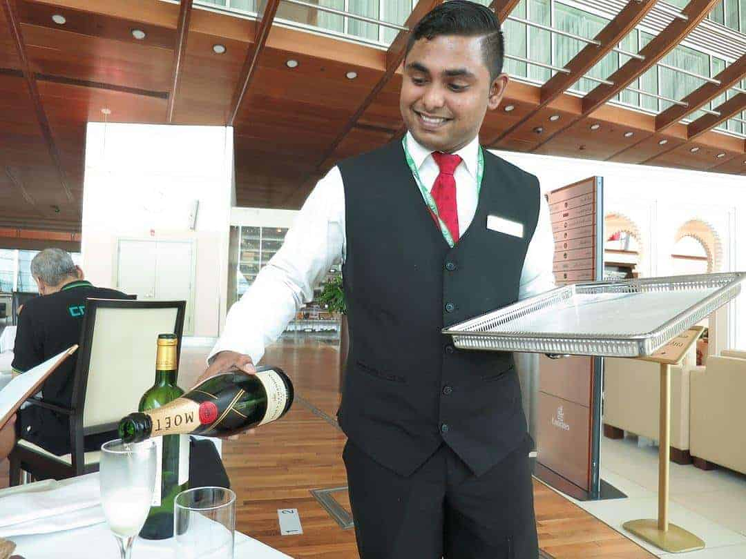 waiter serving champagne at the Emirates First Class Lounge Dubai