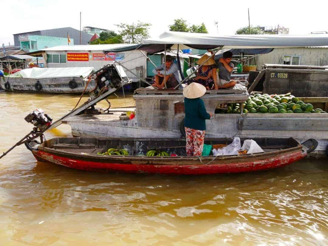 A lady buying her produce from one of the floating market boats