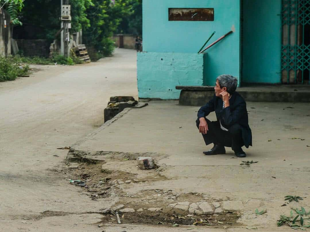 man squatting in vietnam