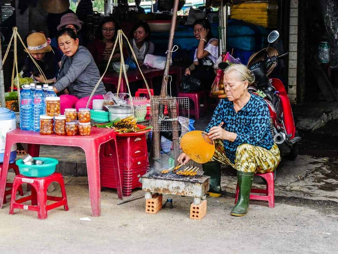 Lady on the street cooking food in Hoi An