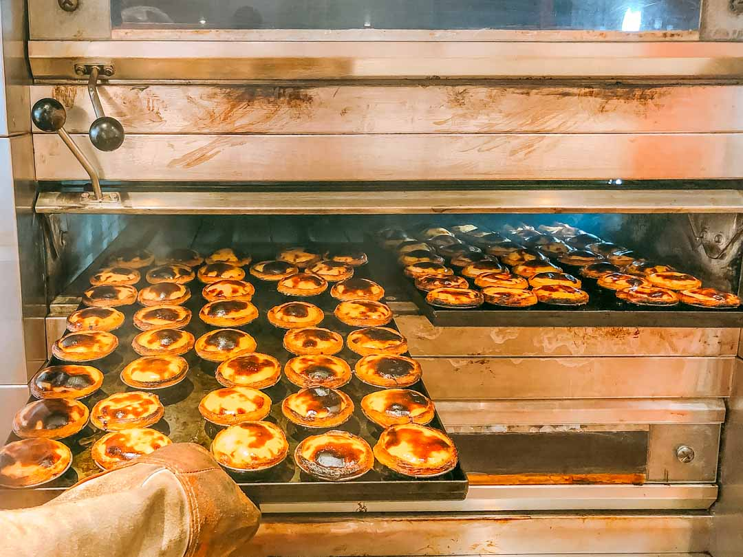 pasteis de nata coming out of oven